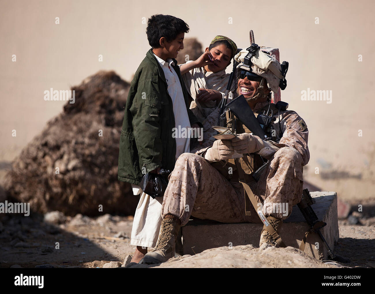 U.S. Marine practices Pashto with Afghan boys in Afghanistan. - Stock Image