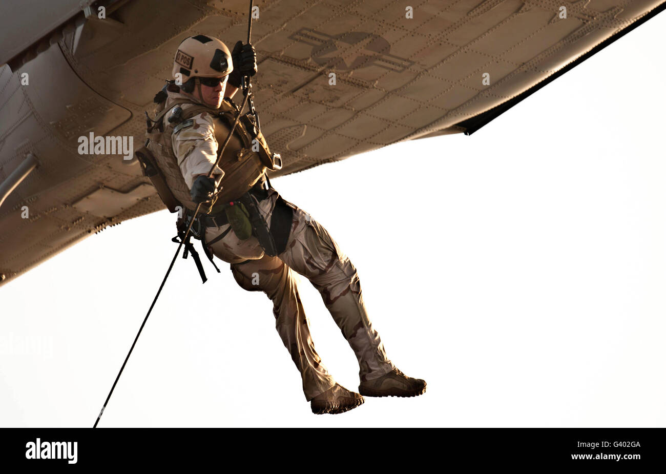 A soldier rappels from an MH-60S Knighthawk helicopter. Stock Photo