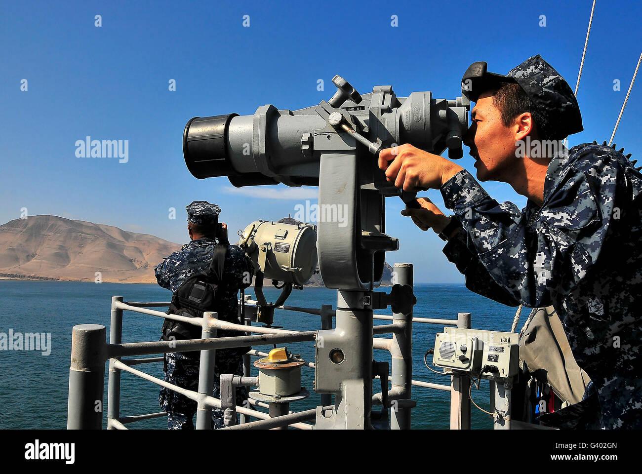 U.S. Navy sailors observe the coastline from aboard USS Bunker Hill. - Stock Image