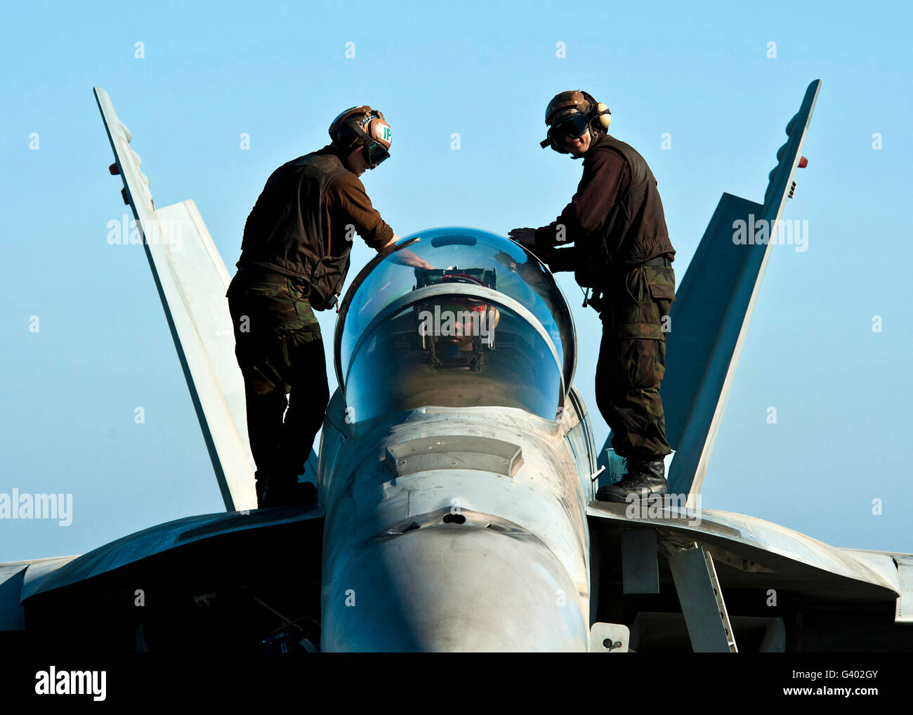 U.S. Navy sailors wipe down the canopy of an F/A-18F Super Hornet. Stock Photo
