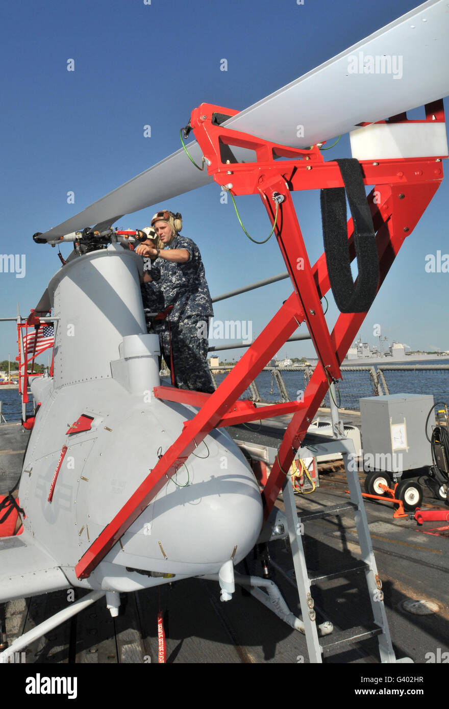 U.S. Navy mechanic removes a rotor blade from a MQ-8B Fire Scout. - Stock Image