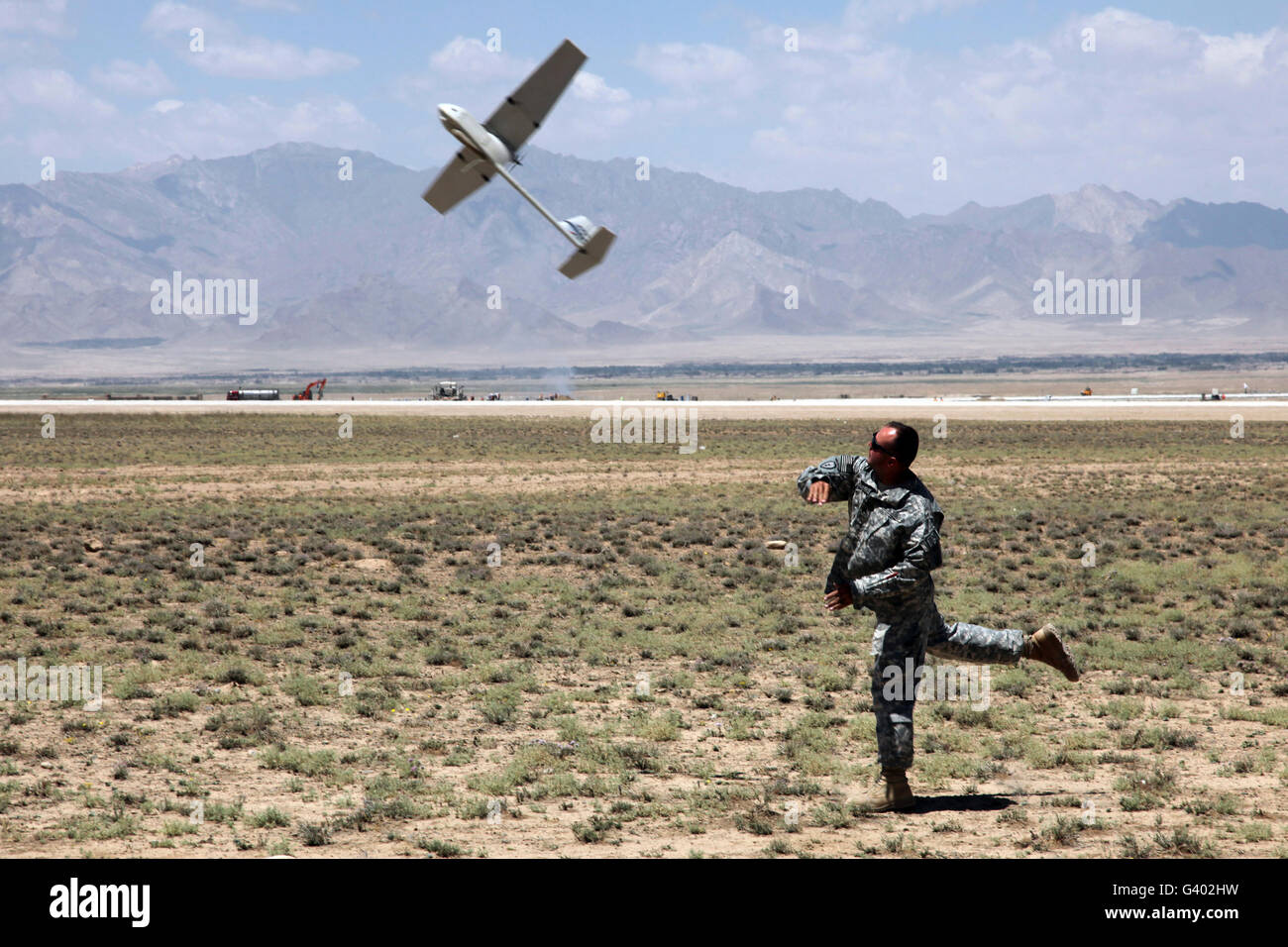 U.S. Army soldier launches an RQ-11 Raven unmanned aerial vehicle. - Stock Image