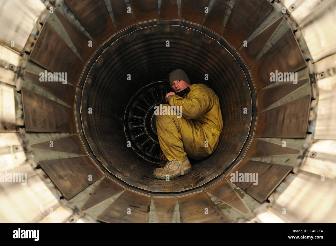 An aircraft technician inspects the exhaust of an F-16 Fighting Falcon. - Stock Image