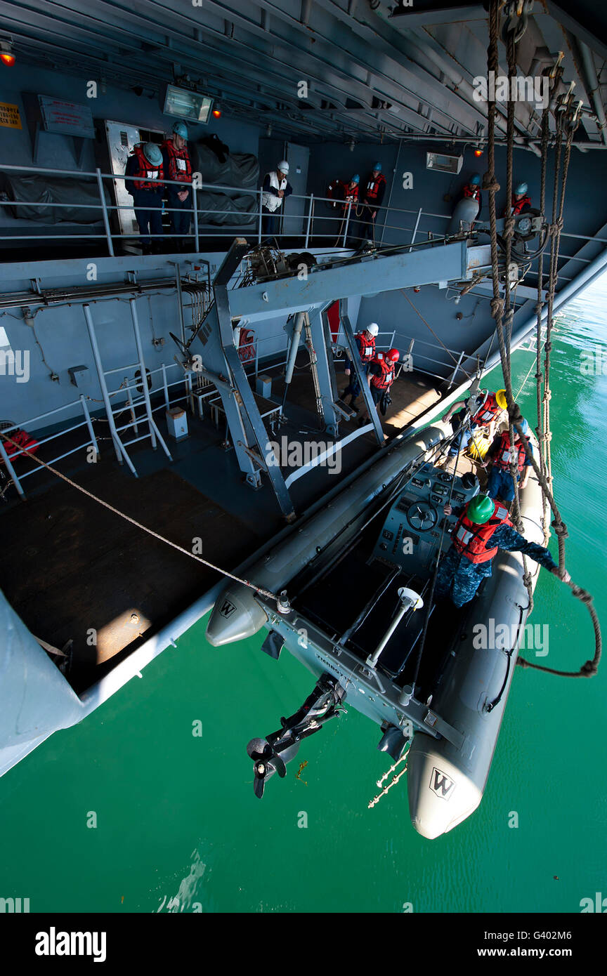 Crew members enter the starboard rigid-hull inflatable boat. - Stock Image