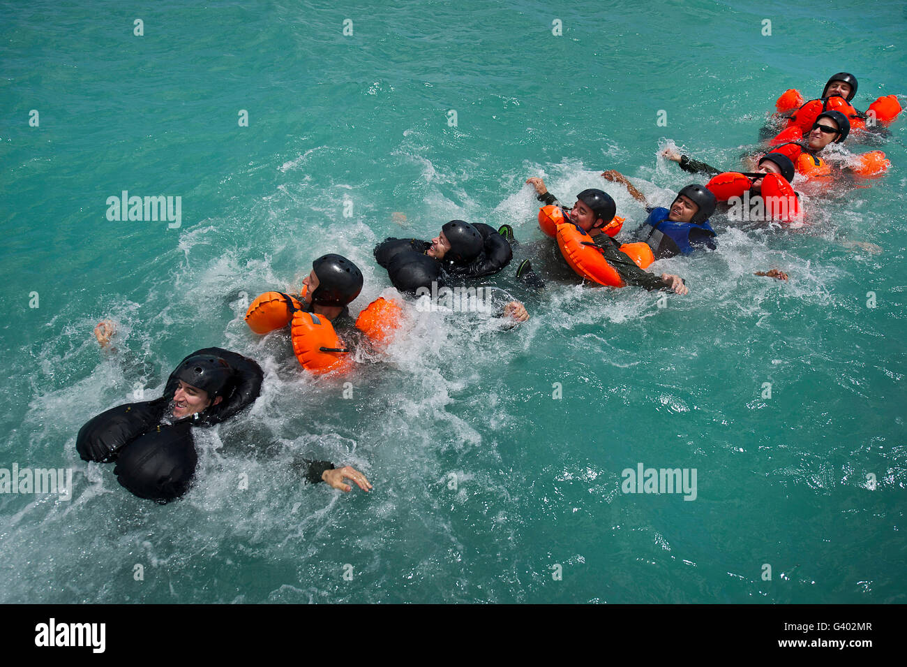 Group swimming technique during a water survival refresher class. - Stock Image