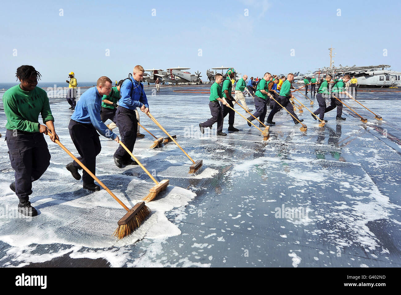 Sailors scrub down the flight deck of USS Abraham Lincoln. Stock Photo