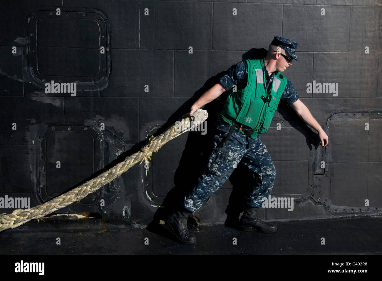 Fire Control Technician hauls a heavy line from the harbor tug. - Stock Image