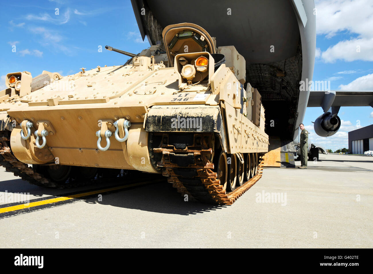 An M2/M3 Bradley fighting vehicle drives toward a C-17 cargo bay. - Stock Image
