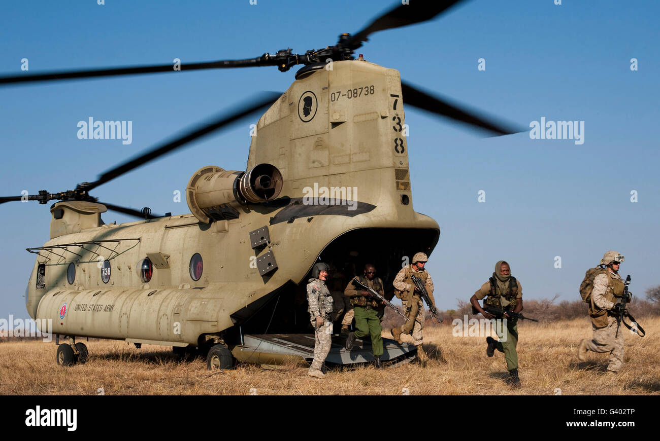 U.S. Marines exit a Hawaii Army National Guard CH-47F Chinook helicopter. - Stock Image