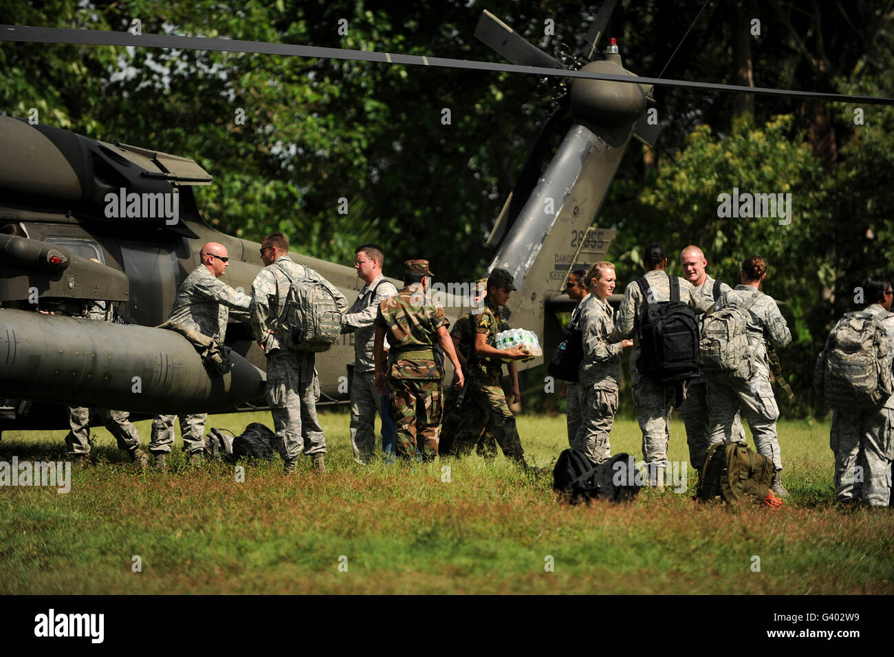 Soldiers unload medical supplies, food and water from a UH-60 Blackhawk. - Stock Image