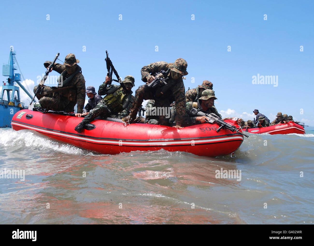 U.S. Marines and Philippine Marines ride in Philippine coast Guard zodiac boat. - Stock Image
