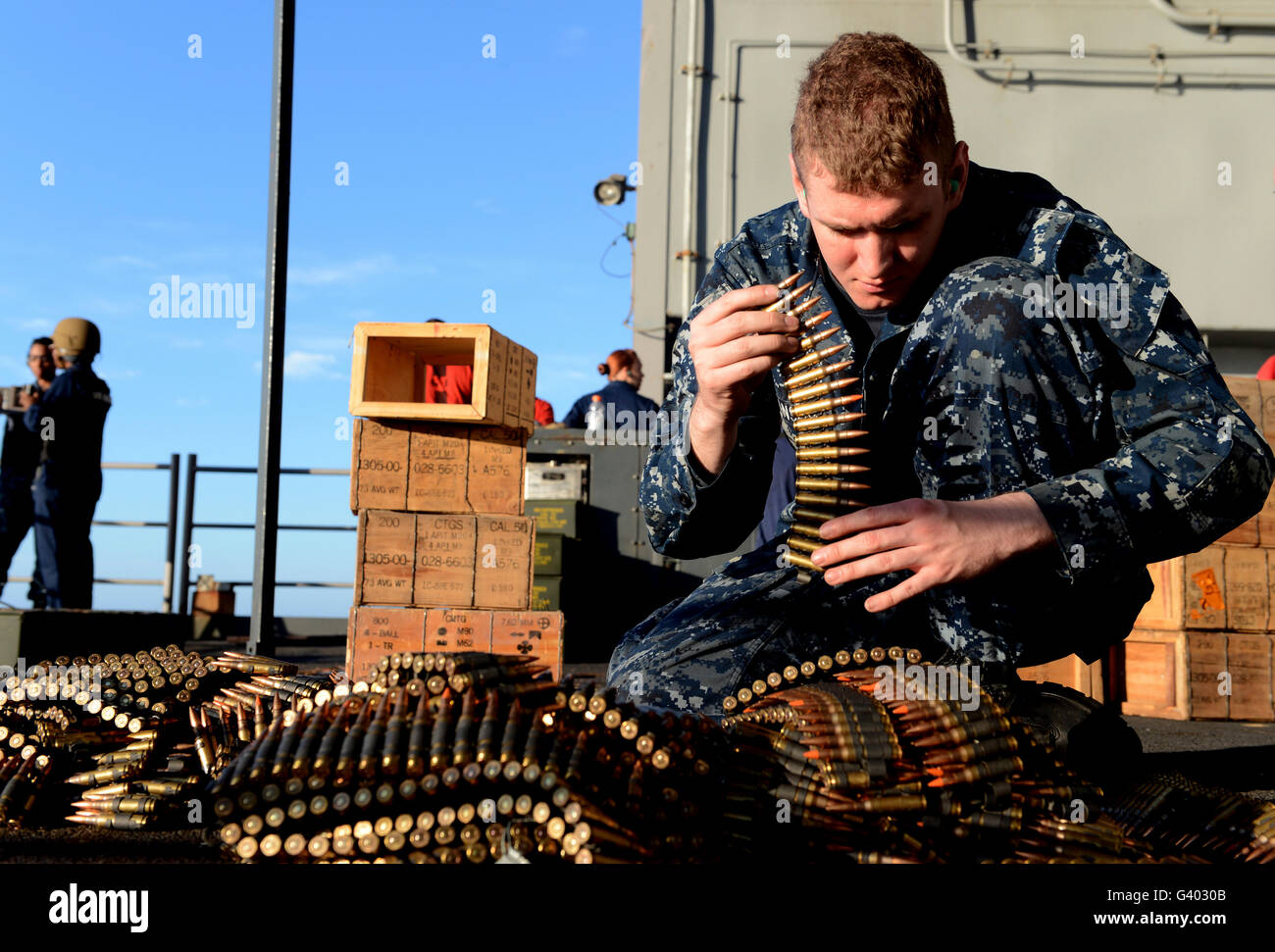 Gunner's Mate sorts ammunition during a live fire training exercise. Stock Photo
