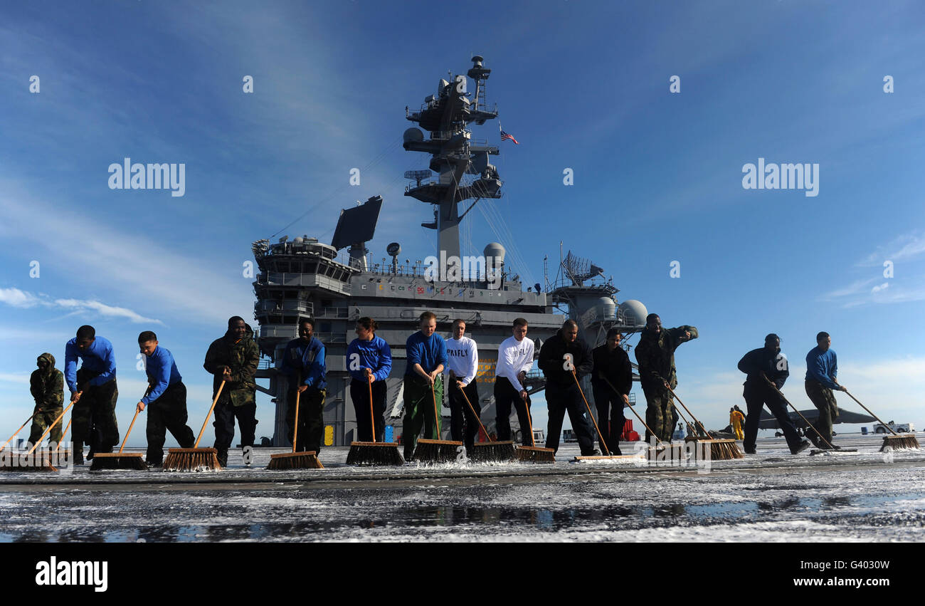Sailors participate in a fight deck scrubbing exercise aboard USS Carl Vinson. - Stock Image