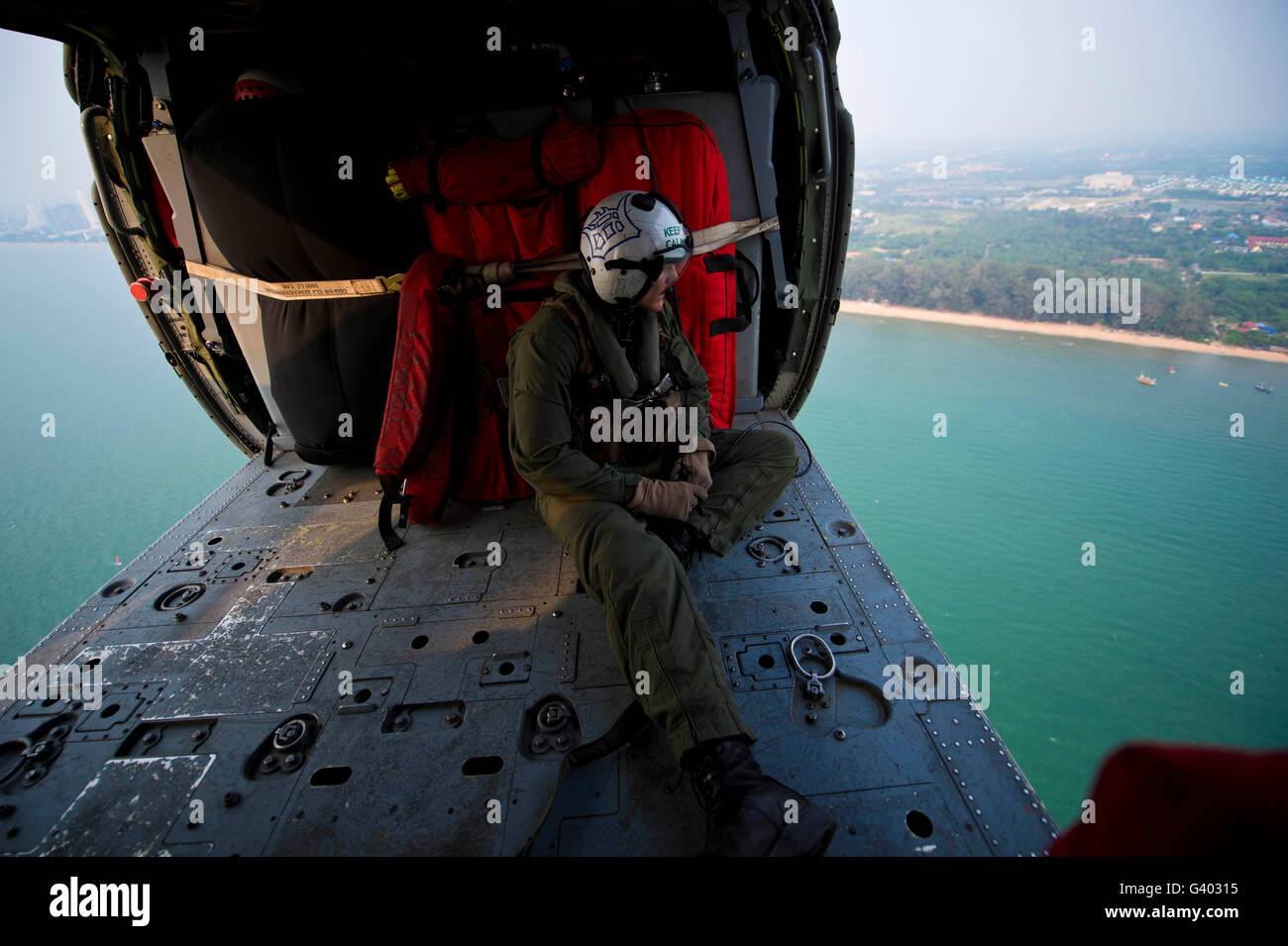 Naval Aircrewman surveys the Gulf of Thailand from an MH-60S Sea Hawk. - Stock Image
