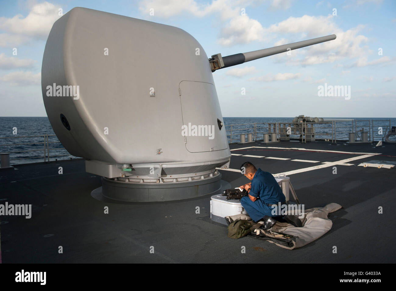 Seaman performs maintenance on a .50-caliber machine gun. - Stock Image