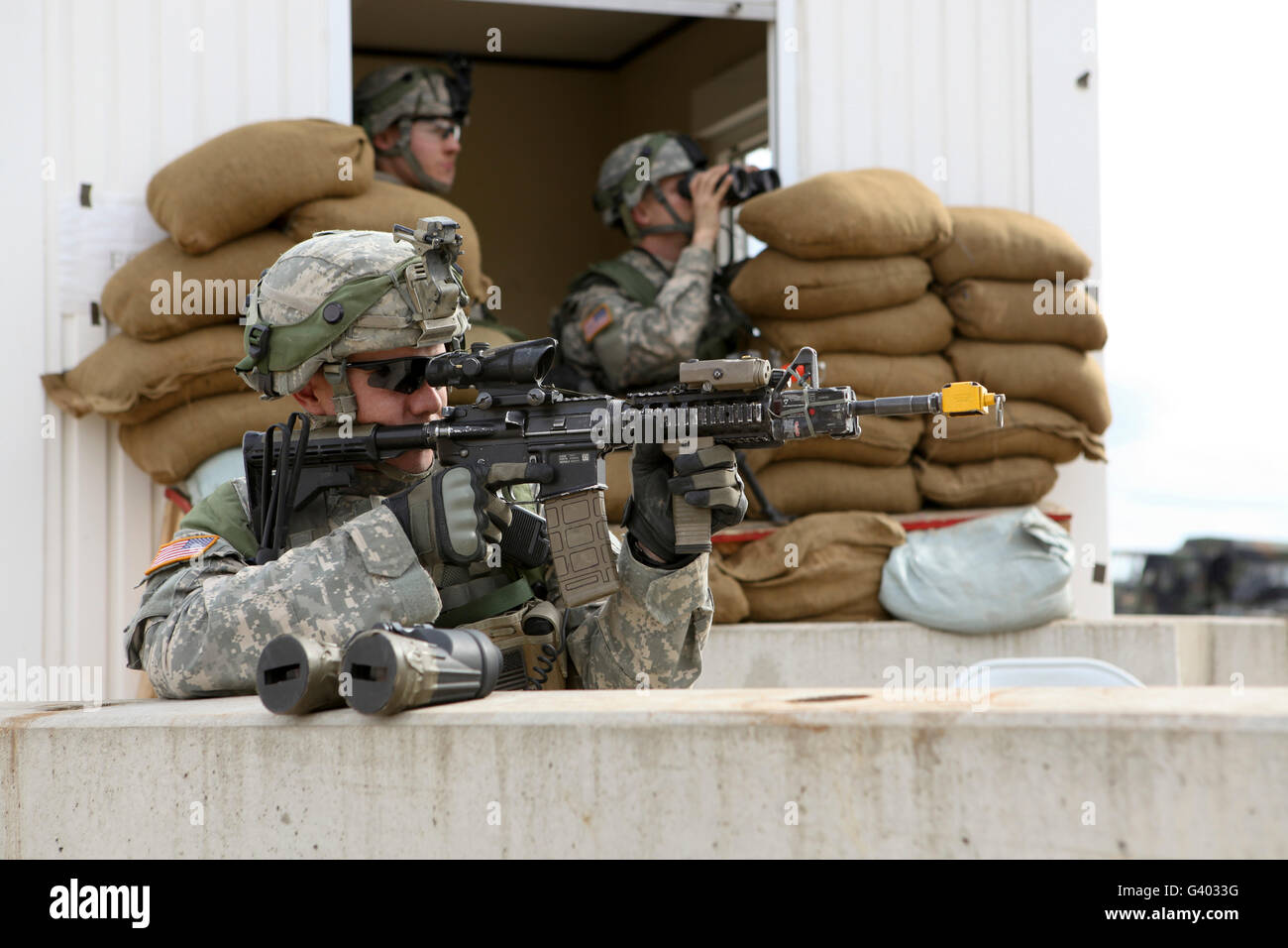 U.S. Army soldier looks down the scope of his M4 assault rifle. - Stock Image