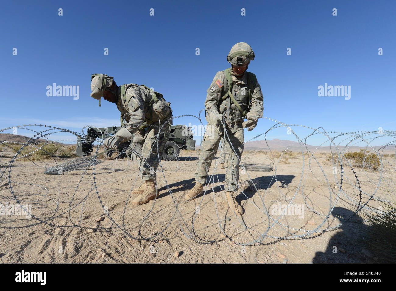 Soldiers uncoil concertina wire at Fort Irwin, California. - Stock Image