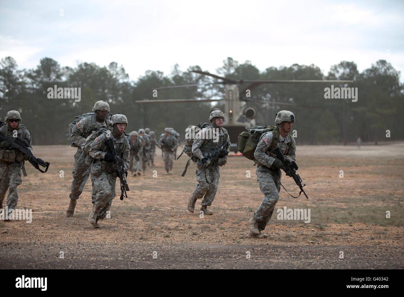 Soldiers exit a CH-47 Chinook helicopter at Fort Benning, Georgia. - Stock Image