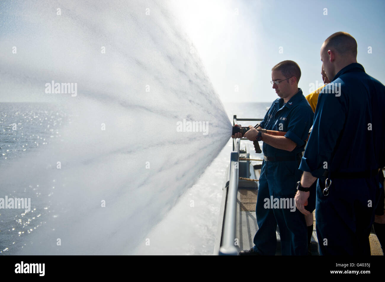 Logistics Specialist practices fire hose handling. - Stock Image
