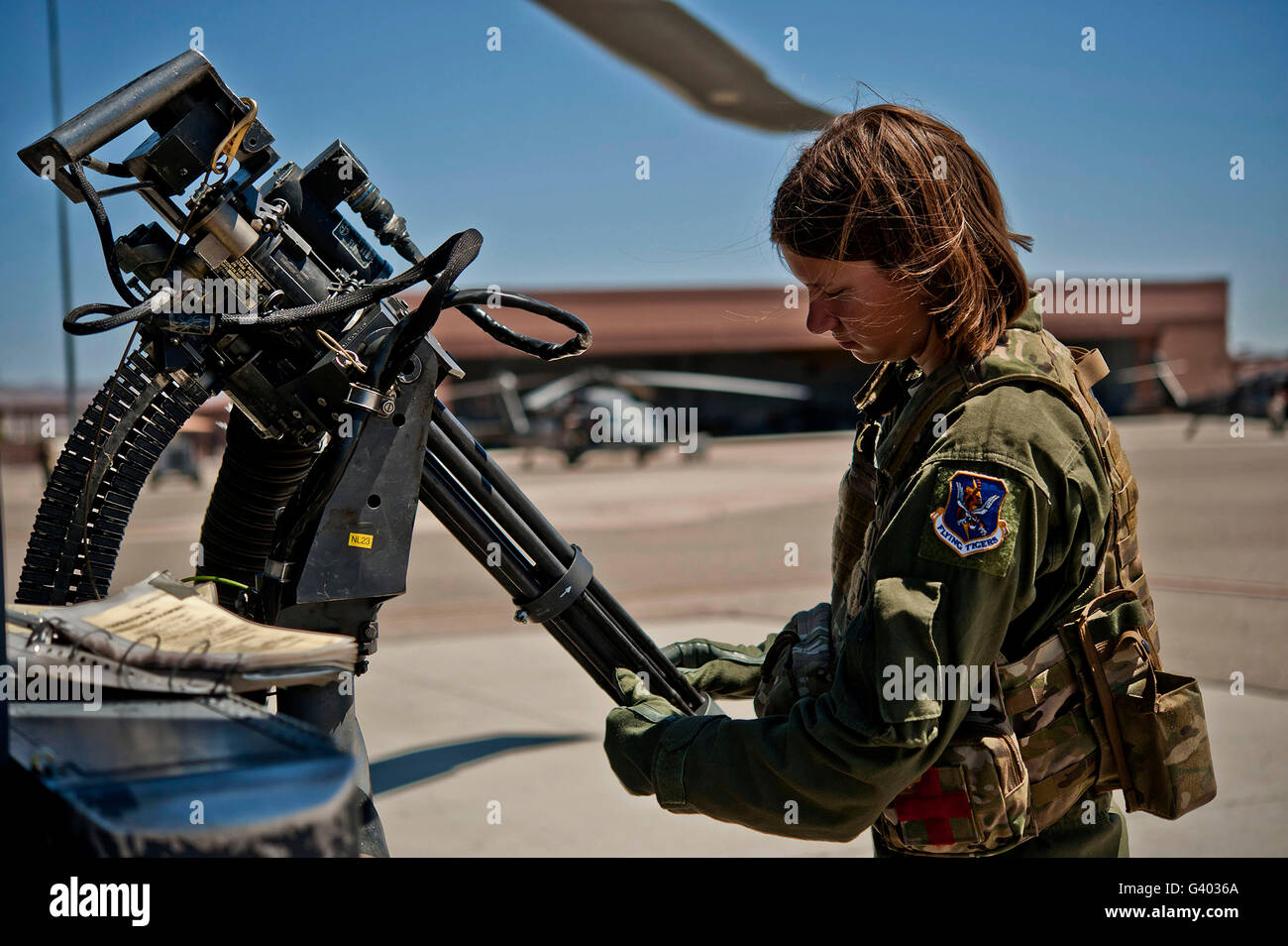 Airman examines the barrels of a GAU-2 mini gun on an HH-60 Pave Hawk. - Stock Image