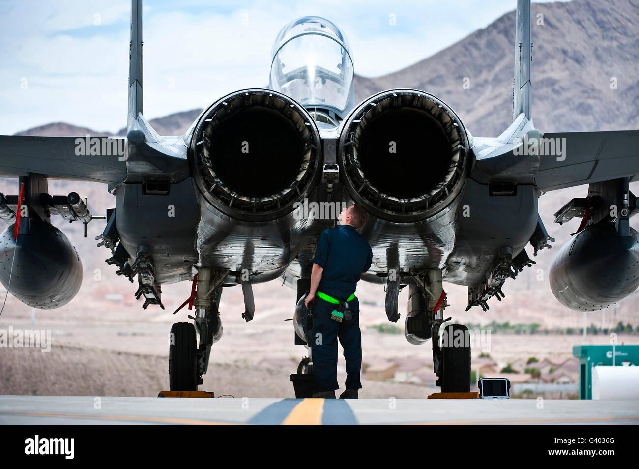 Airman inspects an F-15E Strike Eagle. - Stock Image
