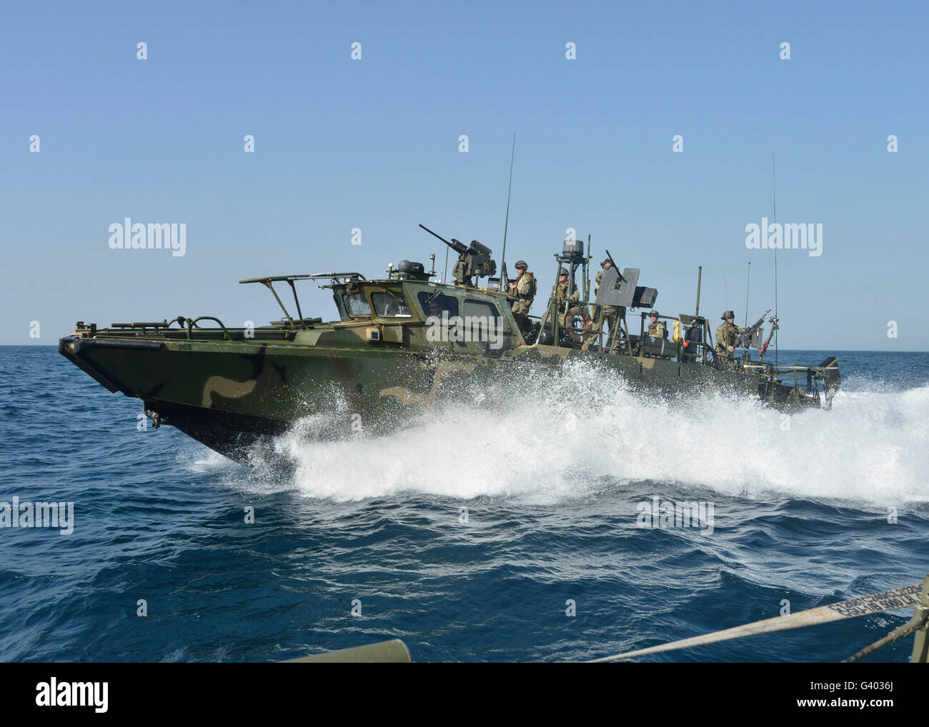 A riverine command boat transits open water. - Stock Image