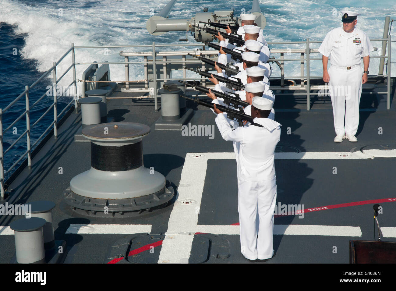 Sailors render a rifle volley aboard USS Hue City. - Stock Image
