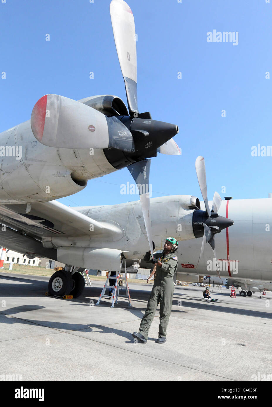 Naval Aircrewman inspects the propellers on a P-3C Orion. - Stock Image