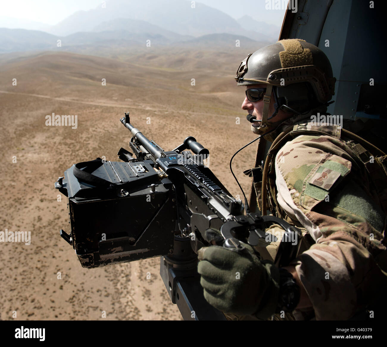 Door gunner scans the terrain over Afghanistan. - Stock Image