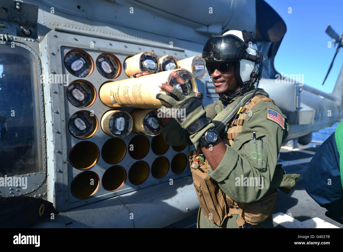 Naval Aircrewman loads a sonar buoy into an MH-60R Sea Hawk helicopter. - Stock Image