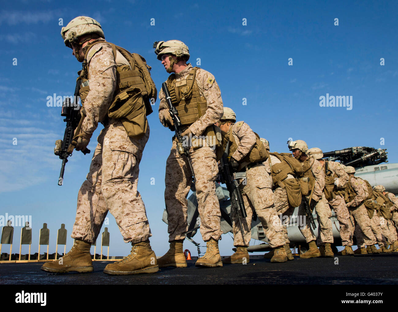 U.S. Marines pivot into position during a live-fire exercise. - Stock Image