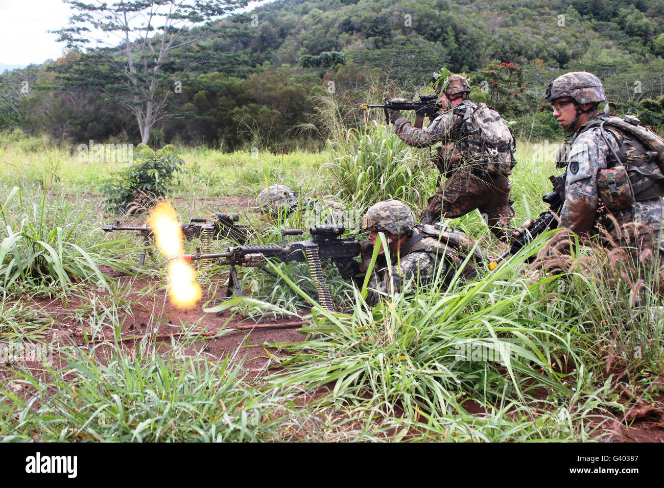 Infantryman fires a burst from his M240B machine gun. - Stock Image
