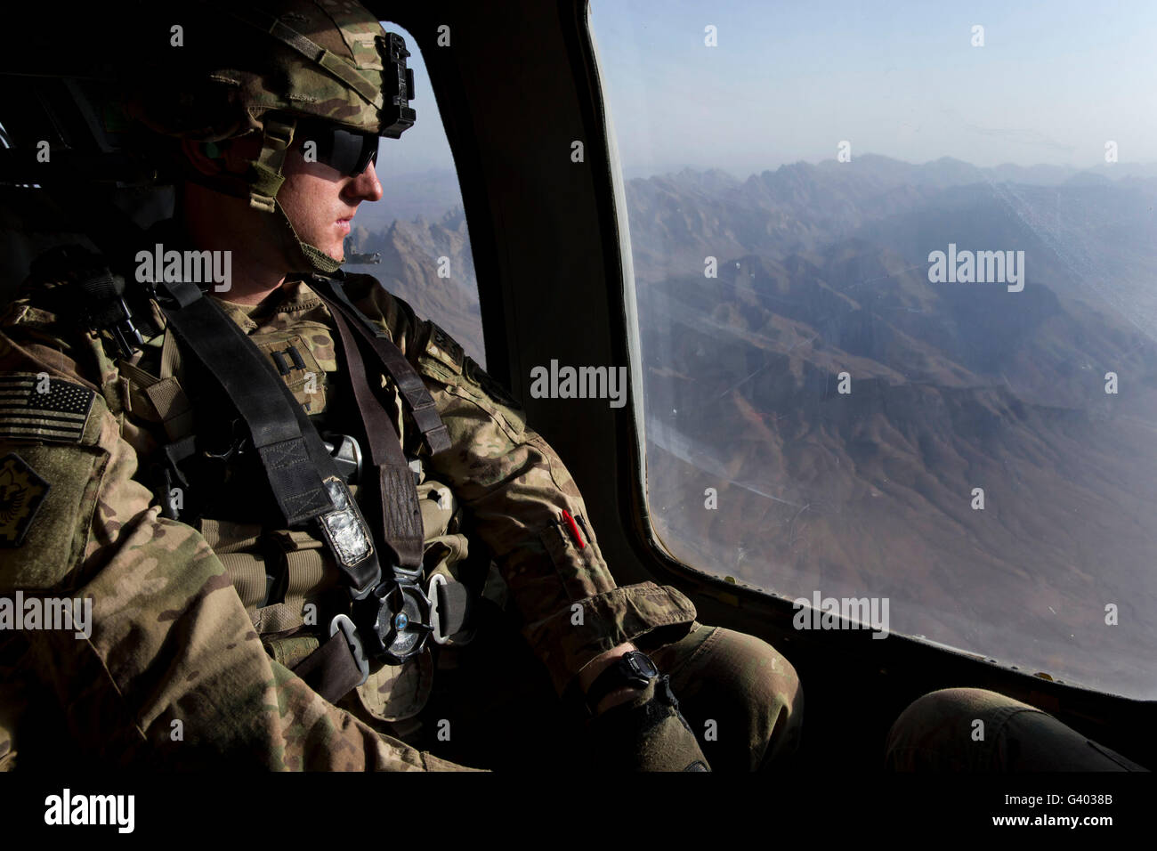 U.S. Army soldier looks out the window of a UH-60 Black Hawk helicopter. - Stock Image