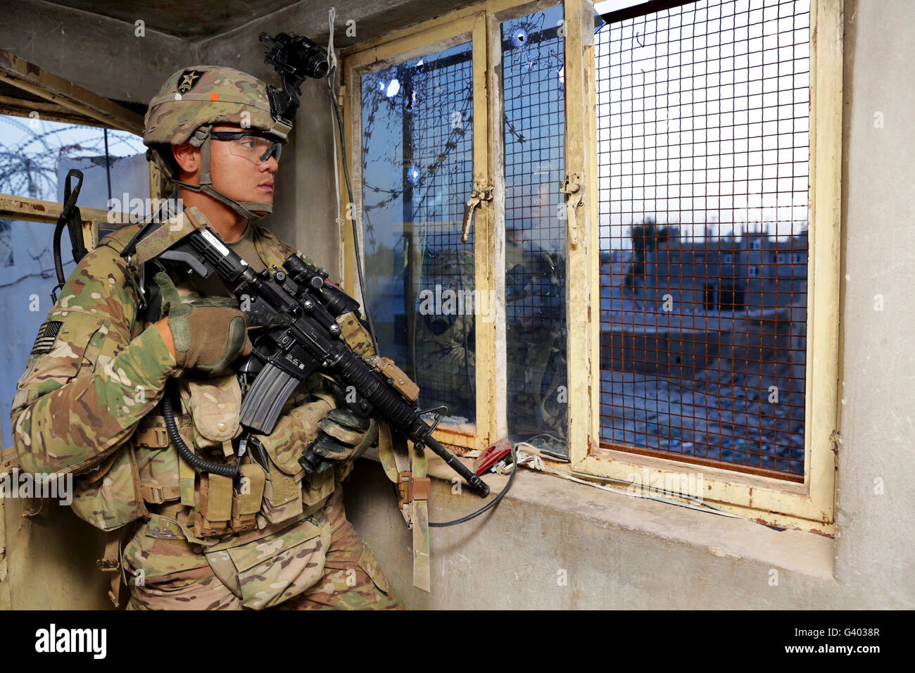 U.S. Army Specialist monitors his surroundings from a guard post. - Stock Image