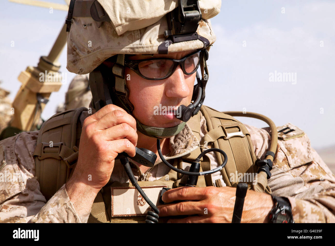 U.S. Marine talks over the radio in Afghanistan. - Stock Image