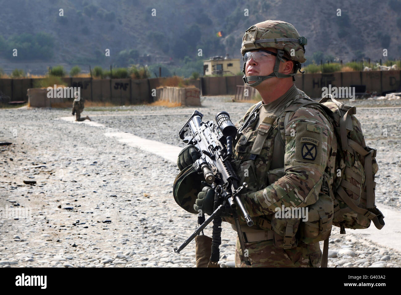 U.S. Army soldier provides overwatch at an airfield in Afghanistan. - Stock Image