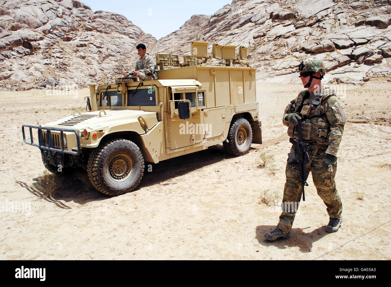 U.S. Air Force soldier guides an Afghan Border Police vehicle. - Stock Image