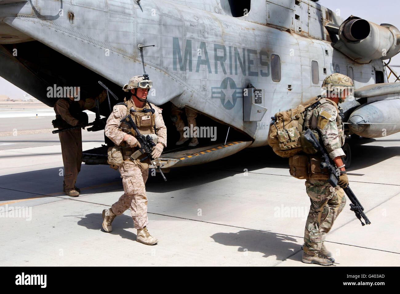 U.S. Marines and British soldiers exit a CH-53E Super Stallion. - Stock Image