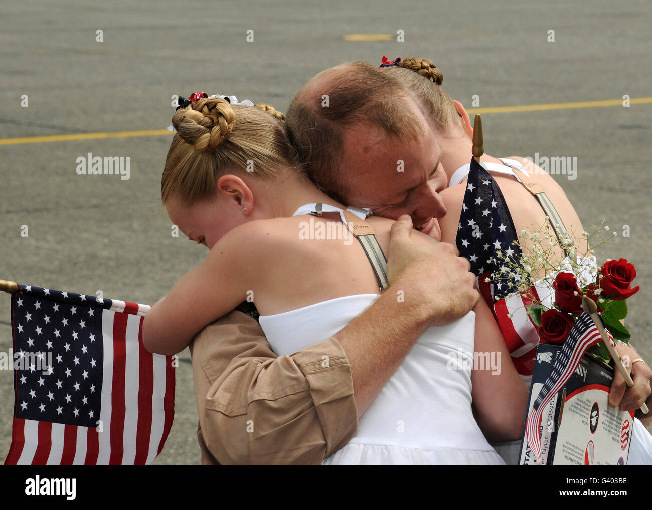 A flight engineer is greeted by his daughters during homecoming. - Stock Image