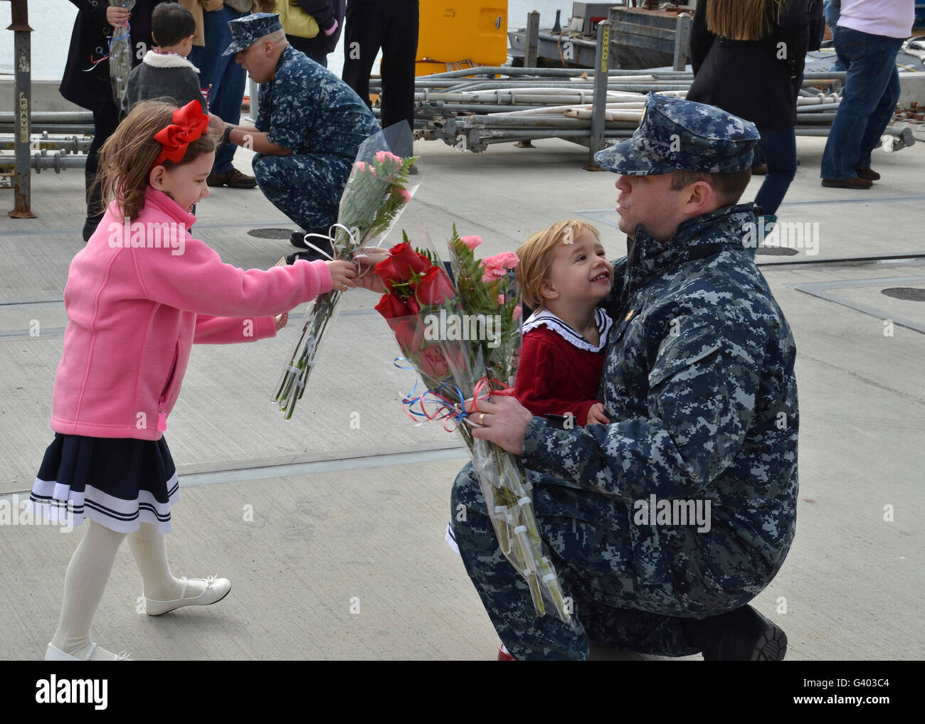 U.S. Navy sailors are greeted by their families during homecoming. - Stock Image