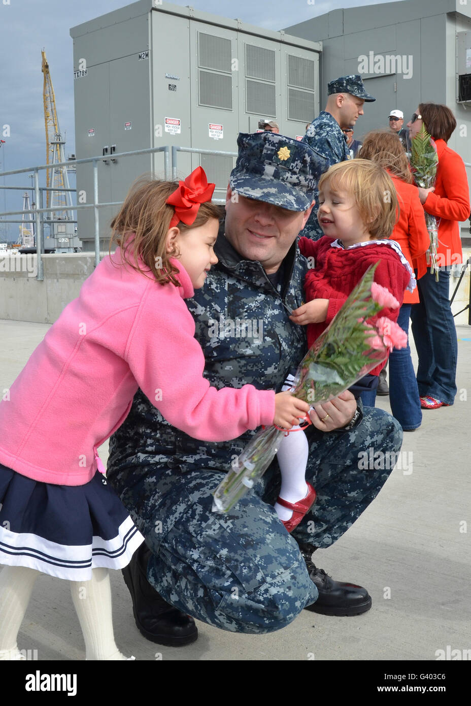 U.S. Navy sailors embrace their loved ones during homecoming celebration. - Stock Image