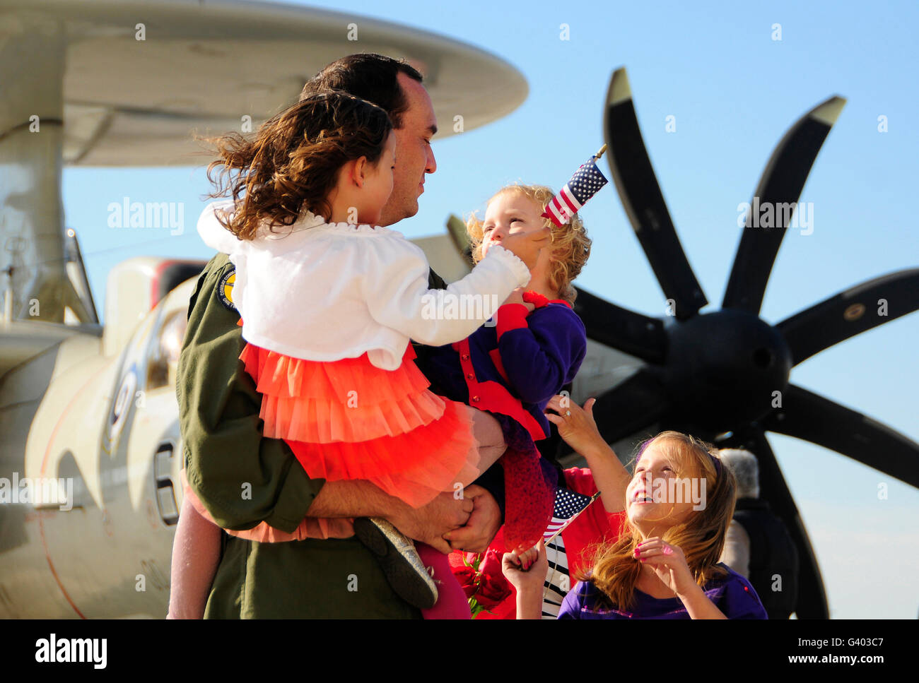 U.S. aviator is greeted by his daughters during the squadron's homecoming. - Stock Image