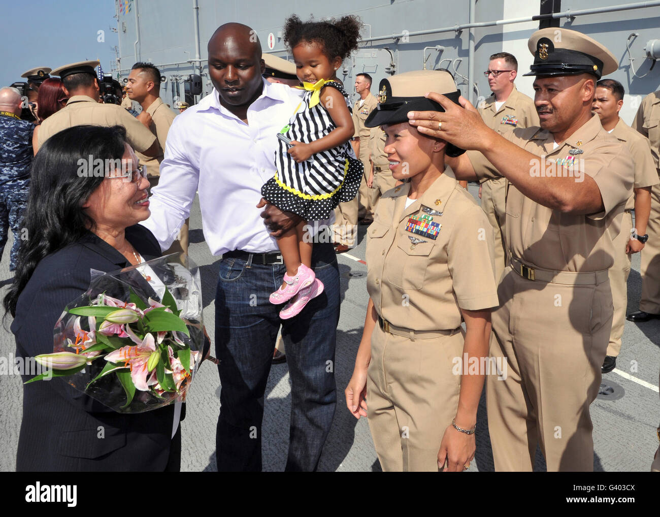 Family members gather around chief petty officer ashe receives her combination cover. - Stock Image