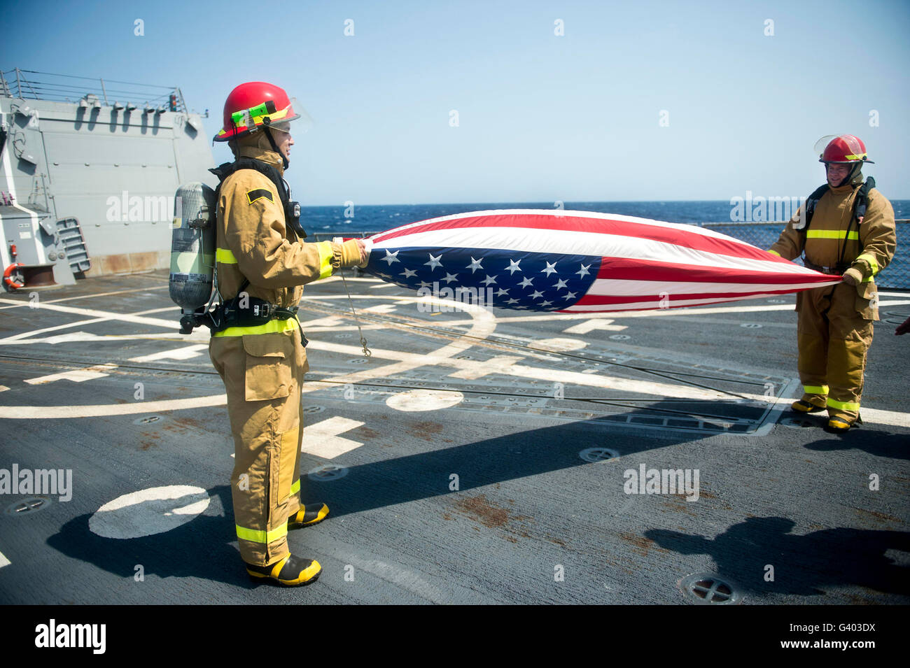 Firemen fold the American flag aboard USS William P. Lawrence. - Stock Image
