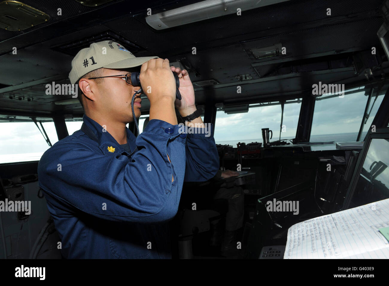 Lieutenant looks for contacts from the pilot house aboard USS Theodore Roosevelt. - Stock Image