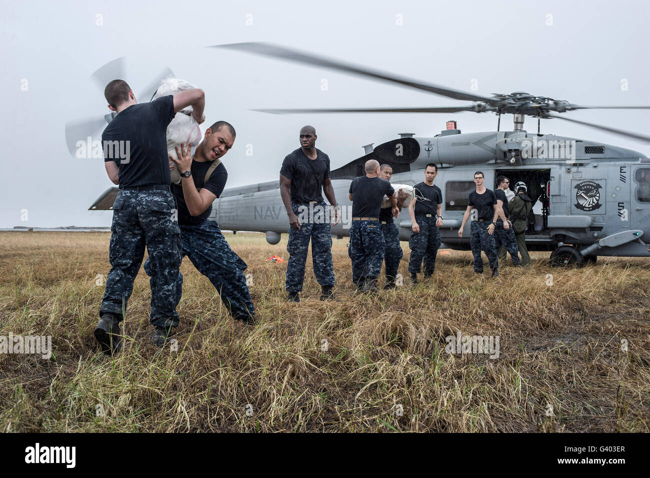Sailors load relief supplies onto an MH-60R Sea Hawk helicopter. - Stock Image