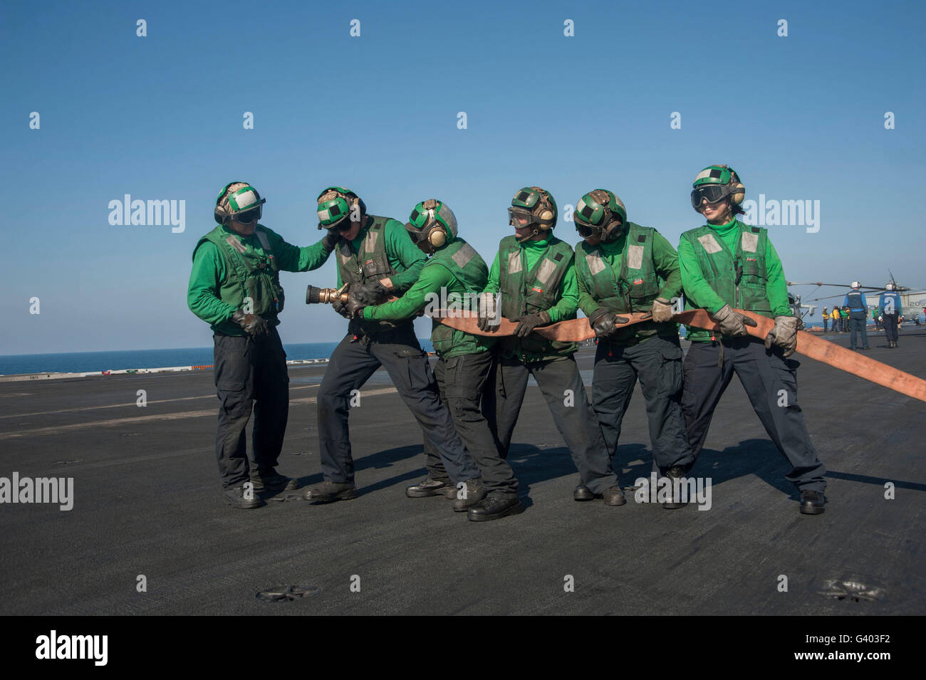 Sailors fight a simulated fire on the flight deck of USS Harry S. Truman. - Stock Image