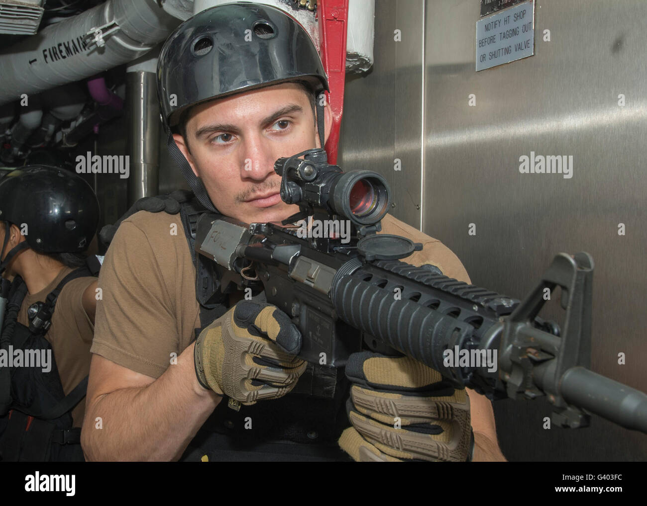 Member of the visit, board, search and seizure team providing cover. - Stock Image