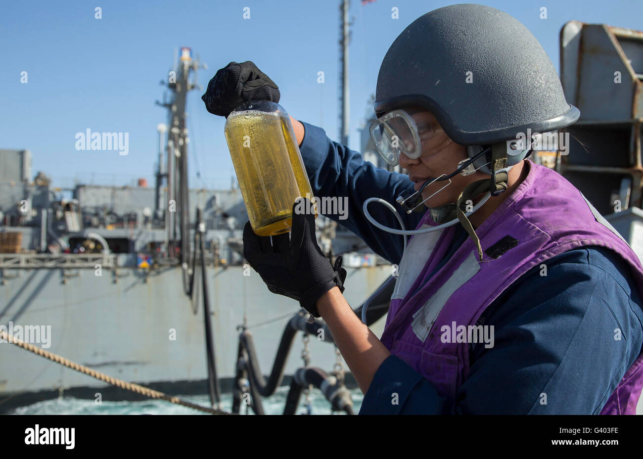Gas Turbine Systems Technician inspects a fuel sample. - Stock Image