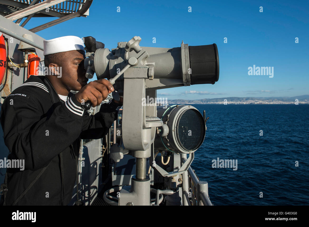 Seaman stands lookout watch on USS Philippine Sea. - Stock Image